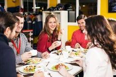 Gente que se sienta en la tabla de banquete Imagenes de archivo