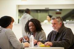 Gente que se sienta en la tabla que come la comida en refugio para personas sin techo Fotografía de archivo libre de regalías