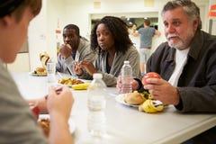 Gente que se sienta en la tabla que come la comida en refugio para personas sin techo Fotos de archivo