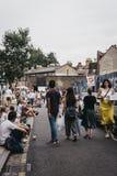 Gente que se sienta en la tierra en la calle de Erza, relajándose después de visitar el mercado de la flor del camino de Columbia fotografía de archivo libre de regalías