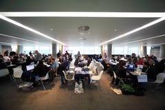 Gente que se sienta en pasillo de reunión en congreso de CEPIC Imágenes de archivo libres de regalías