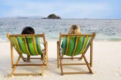 Gente que se sienta en sillas en la playa Foto de archivo libre de regalías