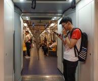 Gente que se sienta en tren del BTS en Bangkok, Tailandia fotografía de archivo