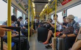 Gente que se sienta en tren del BTS en Bangkok, Tailandia foto de archivo