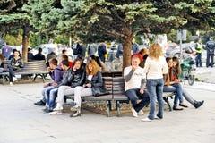 Gente que se sienta en un banco de parque en Bitola imagen de archivo