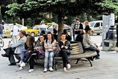 Gente que se sienta en un banco de parque en Bitola fotos de archivo