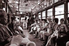Gente que se sienta en un tren de coche histórico de la calle en Kyoto imagenes de archivo