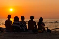 Gente que se sienta en una playa que mira puesta del sol Imágenes de archivo libres de regalías