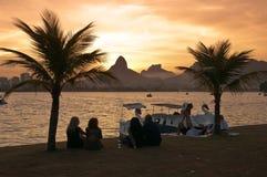 Gente que se sienta entre las palmeras delante del lago y la puesta del sol del reloj fotografía de archivo