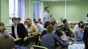 Gente que se sienta junto y que participa en curso de teambuilding Los hombres y las mujeres dentro del cuarto son encargados de almacen de video