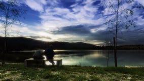 Gente que se sienta por el timelapse del lago almacen de video