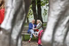 Gente que se sienta, ropa de moda, banco de parque en un CIT moderno fotos de archivo