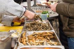 Gente que se sirve de la tabla de comida fría Foto de archivo