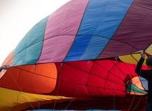 Gente que sostiene el globo del aire caliente durante la inflación foto de archivo