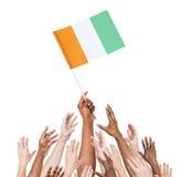 Gente que sostiene la bandera de Cote D'Ivoire Fotografía de archivo
