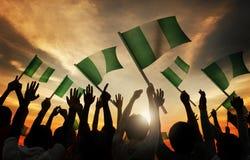 Gente que sostiene la bandera de Nigeria en Lit trasero Foto de archivo libre de regalías