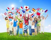 Gente que sostiene las banderas nacionales del mundo imagenes de archivo