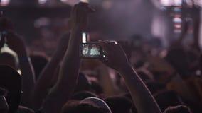 Gente que sostiene sus teléfonos elegantes que tiran el vídeo o la foto metrajes