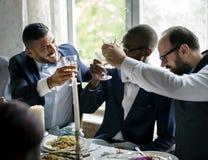 Gente que sostiene sus vidrios del champán para una tostada en una tabla de la boda foto de archivo libre de regalías
