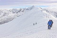 Gente que sube en Kasprowy Wierch de Zakopane en Tatras en wint Foto de archivo