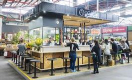 Gente que tiene comidas en barra japonesa con la cocina abierta en Melbourne Imágenes de archivo libres de regalías