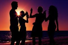 Gente que tiene partido en la playa con las bebidas Foto de archivo libre de regalías