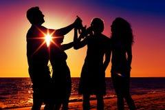 Gente que tiene partido en la playa con las bebidas Fotografía de archivo libre de regalías