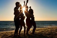 Gente que tiene partido en la playa con las bebidas Imagen de archivo