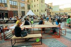 Gente que tiene resto alrededor de las tablas de festival de la comida de la calle en el fin de semana Fotografía de archivo libre de regalías
