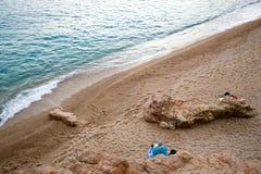 Gente que tiene un resto en una playa abandonada por el mar Imagen de archivo libre de regalías