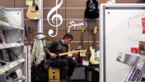 Gente que toca la guitarra dentro de la tienda de Best Buy almacen de metraje de vídeo