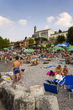 Gente que toma el sol en la playa el 30 de julio de 2016 en Desenzano del Garda, Italia Foto de archivo