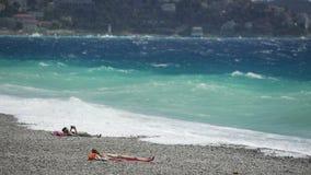 Gente que toma el sol en Pebble Beach, ondas espumosas grandes del océano picado que golpean la orilla metrajes
