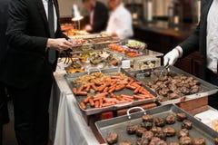Gente que toma la comida en el abastecimiento de la comida fría que cena comiendo el partido Concepto de la comida fría del event Imagen de archivo