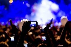 Gente que toma las fotografías con el teléfono elegante del tacto durante una música imagen de archivo