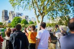 Gente que toma las fotos de la catedral de Notre Dame sin el tejado y el chapitel imagen de archivo libre de regalías