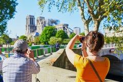 Gente que toma las fotos de la catedral de Notre Dame sin el tejado y el chapitel fotografía de archivo libre de regalías