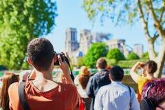 Gente que toma las fotos de la catedral de Notre Dame sin el tejado y el chapitel fotos de archivo