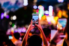 Gente que toma las fotos de muchedumbres con el teléfono móvil imagen de archivo