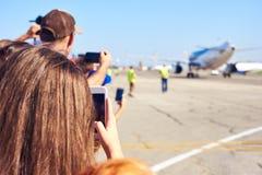 Gente que toma las fotos del aeroplano con sus smartphones imagen de archivo