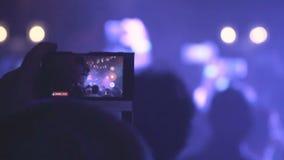 Gente que toma las fotos o que registra el vídeo con sus teléfonos elegantes en el concierto de la música metrajes