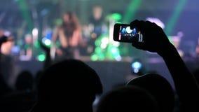 Gente que toma las fotos o que registra el vídeo con sus teléfonos elegantes en el concierto de rock de la música en un club de n almacen de video