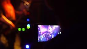 Gente que toma las fotos o que registra el vídeo con sus teléfonos elegantes en la cámara lenta del concierto de la música almacen de video