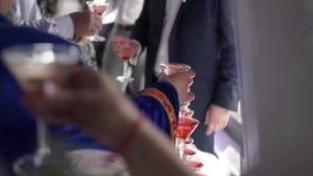 Gente que toma los vidrios de vino espumoso en el partido almacen de metraje de vídeo