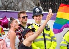 Gente que toma Selfie con el oficial de policía At Pride Parade Imagenes de archivo