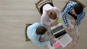 Gente que trabaja con el ordenador portátil y los documentos metrajes