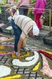 Gente que trabaja en la alfombra de flores Imagen de archivo libre de regalías
