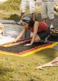 Gente que trabaja en la alfombra de flores Imágenes de archivo libres de regalías
