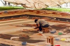 Gente que trabaja en la alfombra de la arena Foto de archivo