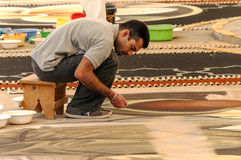 Gente que trabaja en la alfombra de la arena Imagen de archivo libre de regalías